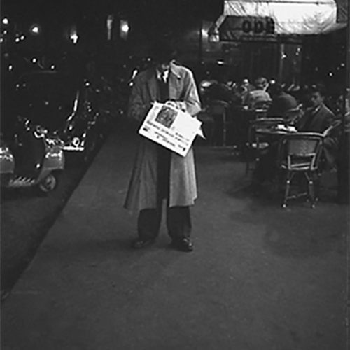 Man_reading_outside_cafe_at_night_Paris_1952500px_
